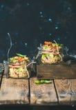 Homemade quinoa salad with tomatoes, avocado, basil in jars. Homemade jar quinoa salad with cherry tomatoes, sun-dried tomatoes, avocado and basil. Detox Royalty Free Stock Photo