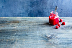 Homemade raspberry jam. And fresh raspberries on vintage table, dark concrete wall background, copy space, selective focus Stock Photo