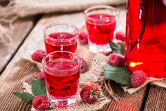 Homemade Raspberry Liqueur. In a glass with some fresh fruits Royalty Free Stock Photos