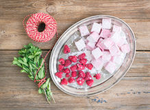 Homemade raspberry marshmallow with fresh raspberries, sugar pow. Der and a bunch of fresh mint on a silver dish over a rustic wood background Royalty Free Stock Photo