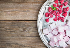 Homemade raspberry marshmallow with fresh raspberries and sugar. Powder on a silver dish over a rustic wood background with a cope space Stock Photos