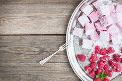 Homemade raspberry marshmallow with fresh raspberries and sugar. Powder on a silver dish over a rustic wood background with a cope space Royalty Free Stock Photography