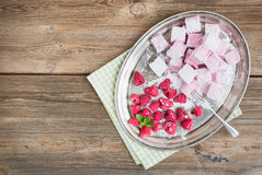 Homemade raspberry marshmallow with fresh raspberries and sugar. Powder on a silver dish over a rustic wood background with a copy space Stock Photo
