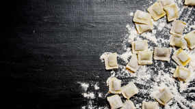Homemade ravioli with flour. On black table with flour. Homemade ravioli with flour. On the black table with flour. Free space for text . Top view Royalty Free Stock Image
