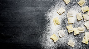 Homemade ravioli with flour. On black table with flour. Homemade ravioli with flour. On the black table with flour. Free space for text . Top view Stock Photo