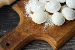 Homemade ravioli and flour on a wooden board Stock Images