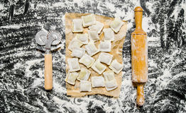 Homemade ravioli with a knife and rolling pin in flour. Stock Photos