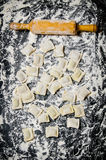 Homemade ravioli with a rolling pin in flour. Royalty Free Stock Photography
