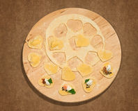 Homemade ravioli in the shape of heart,open and closed, on a round centerpiece in wood. Royalty Free Stock Photos