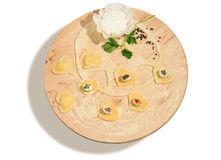 Homemade ravioli in the shape of heart,open and closed, with spiced cheese,fresh ricotta,parsley and a few grains of black pepper. Stock Image