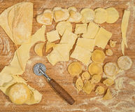Homemade ravioli and tortellini with an ear of wheat and wheel dough cutter. Royalty Free Stock Photos