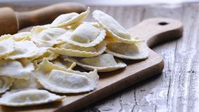 Homemade ravioli on wooden board. Close-up of homemade raw ravioli on wooden board in daylight Royalty Free Stock Photo