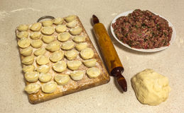 Homemade ravioli on a wooden board, plate of minced meat , doug. Fresh homemade ravioli on a wooden board, next to a plate of minced meat and dough with a Stock Photo