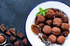Homemade raw chocolate truffles decorated with mint and dark chocolate. Homemade raw chocolate truffles decorated with mint on white plate and pieces of dark Stock Photography