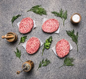 Homemade raw cutlet, on a granite kitchen counter, the concept of cooking burgers, next lined spices and herbs top view Stock Image