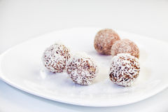 Homemade raw dates truffles with nuts, psyllium and coconut flak. Es on a white plate and white background Stock Photo