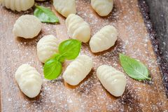 Homemade raw gnocchi  with flour and fresh basil closeup. On a wooden cutting board Royalty Free Stock Photos