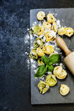 Homemade raw Italian tortellini and basil leaves Stock Images