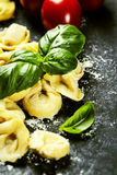 Homemade raw Italian tortellini and basil leaves Stock Photos