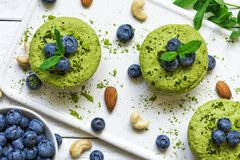 Homemade raw matcha powder cakes with fresh berries, mint, nuts. healthy vegan food concept