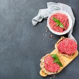 Homemade raw organic minced beef meat and burger cutlet. Healthy food, cooking concept. Homemade raw organic minced beef meat and burger cutlet on a grunge black royalty free stock photography