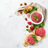 Homemade raw organic minced beef meat burger cutlet and vegetables. Healthy food, cooking concept. Homemade raw organic minced beef meat and burger steak cutlet Royalty Free Stock Photos