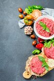 Homemade raw organic minced beef meat burger cutlet and vegetables. Healthy food, cooking concept. Homemade raw organic minced beef meat and burger steak cutlet Royalty Free Stock Image