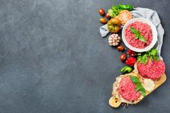 Homemade raw organic minced beef meat burger cutlet and vegetables. Healthy food, cooking concept. Homemade raw organic minced beef meat and burger steak cutlet Stock Images