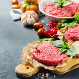 Homemade raw organic minced beef meat burger cutlet and vegetables. Healthy food, cooking concept. Homemade raw organic minced beef meat and burger steak cutlet Stock Photography