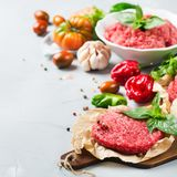 Homemade raw organic minced beef meat burger cutlet and vegetables. Healthy food, cooking concept. Homemade raw organic minced beef meat and burger steak cutlet stock photos