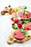 Homemade raw organic minced beef meat burger cutlet and vegetables Stock Images
