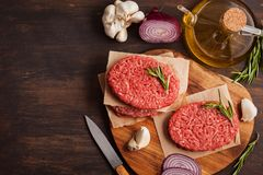 Homemade raw organic minced beef meat steak. Homemade raw organic minced beef meat burger steak on a slate board. Healthy food, cooking blog, classes concept stock photos