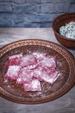 Homemade raw pink beetroot pasta ravioli with cheese and parsley in a plate, on wooden rustic background.  stock photography