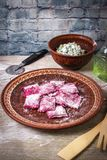 Homemade raw pink beetroot pasta ravioli with cheese and parsley in a plate, on wooden rustic background.  stock image