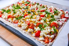 Homemade raw pizza with colorful vegetables and white mozzarella cheese just ready for the oven stock images