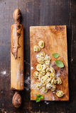 Homemade raw Tortellini. And basil leaves on dark wooden background stock photography