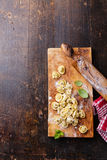 Homemade raw Tortellini and basil leaves Stock Photos