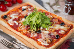 Homemade rectangular pizza on a rustic table Stock Photo