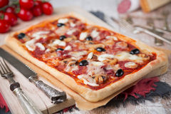 Homemade rectangular pizza on a rustic table Stock Images