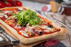 Homemade rectangular pizza on a rustic table Stock Photos