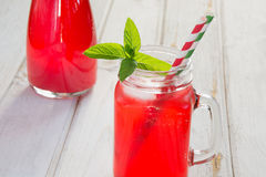 Homemade red currant lemonade in a mason jar with decor on ligth wooden table.