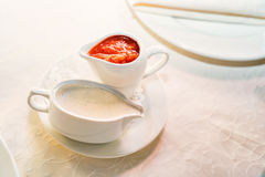 Homemade red and white sauces. Fresh tomato, chili and mayonnaise sauces in white ceramic saucers Stock Photos