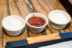 Homemade red and white sauces. Fresh tomato, chili and mayonnaise sauces in white ceramic saucers Royalty Free Stock Photography