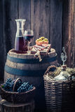 Homemade red wine with olives, cold meats, grapes and demijohn. On old wooden barrel Royalty Free Stock Photos