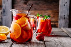 Homemade red wine sangria with orange, apple, strawberry and ice in pitcher and glass on wooden background. Homemade red wine sangria with orange, apple royalty free stock photography