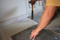Homemade Replacing floor Ceramic tiles broken, and a tile adhesive plaster out the old to cement glue. For a new tile support agai. N on same area royalty free stock photo