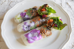 Homemade rice paper rolls with edible flowers. On white plate Stock Photo