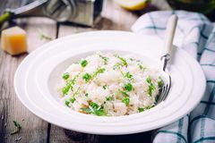 Homemade risotto with chicken, green peas, arugula and parmesan. Selective focus stock photography