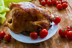 Homemade roast whole chicken. Poultry : homemade roast whole chicken with  tomatoes on wooden background Royalty Free Stock Images
