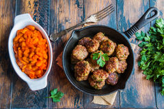 Homemade roasted beef meatballs in cast-iron skillet and beans baked in tomato sauce in baking dish on wooden table in kitchen